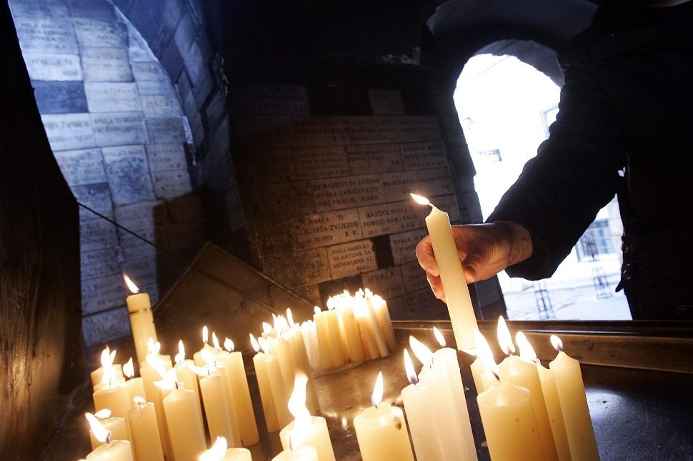 Vjernici pale svijece na Kamenitim vratima