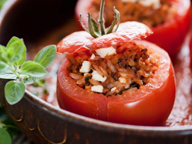 Cheese-Stuffed Tomatoes Recipe That tomatoes go well with cheese is not a secret. As a matter of fact, a small plate of these ingredients, covered with some extra-virgin olive oil, is all it takes to have a tasty appetizer. But if you want to bring things to the next level, you can go for cheese-stuffed tomatoes. It is a delicious version of the aforementioned meal, and a great way to start your Sunday lunch. Here is how you prepare it! What you will need 4 large tomatoes 1 onion 6 spoons of rice 2 spoons of parmesan 2 spoons of soft cow cheese (in souse) 2 cloves of garlic A handpick of black olives A few leafs of fresh oregano Olive oil Cheese-Stuffed Tomatoes Preparation Let's begin with tomatoes. Take a larger knife and cut their upper parts. Next, use a spoon to extract their juicy interior, thus making the pod for stuffing. Don't throw the removed parts, they will be used later! Add some salt and olive oil on the inner side of the tomato. Cook the rice in salted water. As for olives, remove the pips, and mince the meaty parts. Cut onion on small pieces, and fry them on olive oil until they receive a slightly golden and transparent texture. Next, insert the tomato interiors you removed at the beginning of the preparation. Once it vaporizes, add cooked rice and minced olives. Remove from flame and add cheeses. If you have access to Croatian merchandise, we suggest buying the cow cheese called grabancijas. In addition, spice things up with oregano and pepper. Optionally, you can add some more salt, but beware; the cheeses are salty by default. The mixture you receive should be used as stuffing for the tomatoes. You may return the chopped parts. Oil some baking pan, align the cheese-stuffed tomatoes, and bake in heated oven at 180°C for 30 minutes. Dobar Tek!